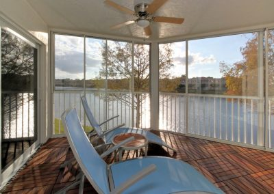Example photo of a screened in patio interior showing a lake view